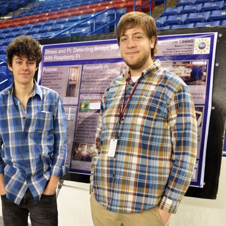 Two male students standing in front of an undergraduate research board
