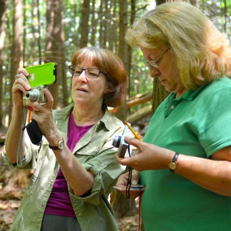 Two women wearing glasses and inspecting handheld cameras