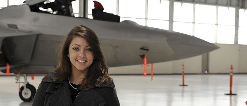 student posed with airplane