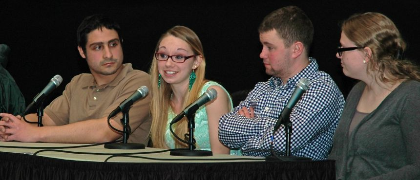 Four students sit at a table during a panel discussion.
