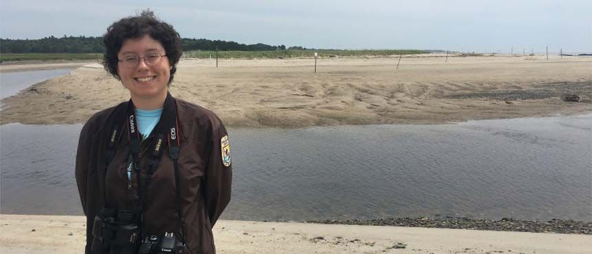Photo of Molly Jacobson standing in front of tidal flats