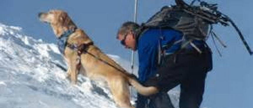 Randy Pierce hikes a snow-covered steep accompanied by his working dog.