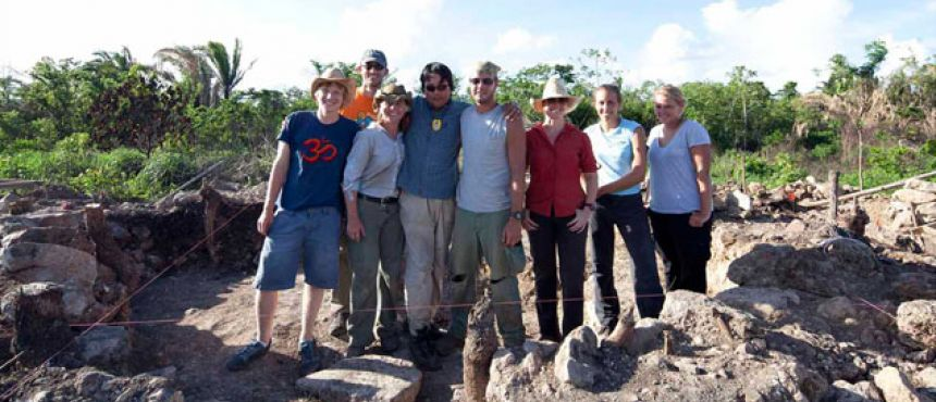 A group of people standing in a small archaeological dig site.