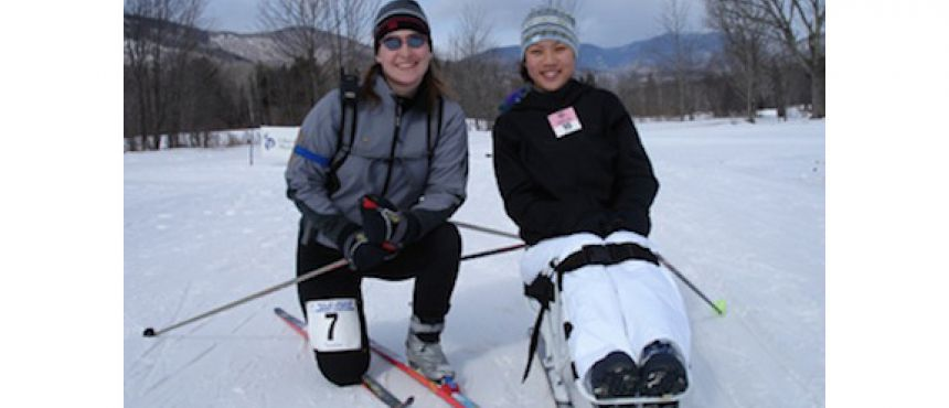 Two skiers, one seated in an adaptive sled, pose on a snow-covered trail.