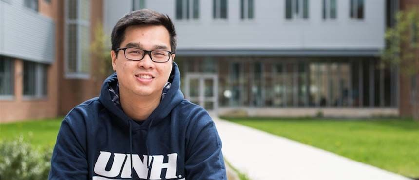 Photo of Thanh Dinh in front of UNH building