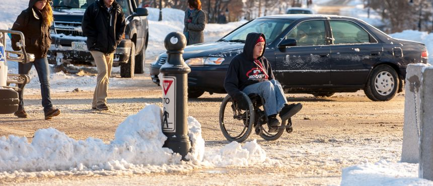 A photograph of a wheelchair user navigating UNH in the snow