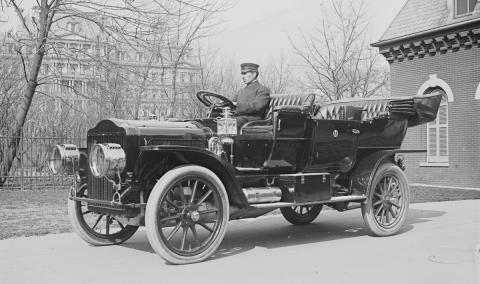 antique picture of a man driving an old car