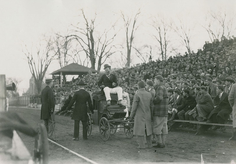 1928 Mayoralty campaign candidate riding in a car with managers standing around in front of crowds in the stands