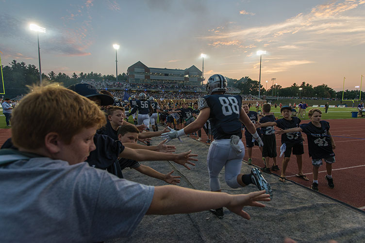 kids high-fiving UNH football players at Wildcat Stadium