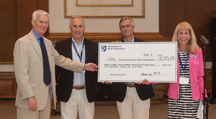 UNH President Mark Huddleston and members of the class of 1977 with their reunion class gift check for UNH