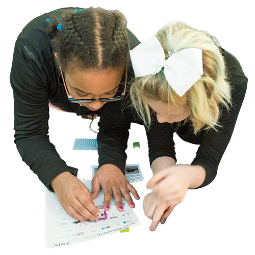 two young girls working on a project at school