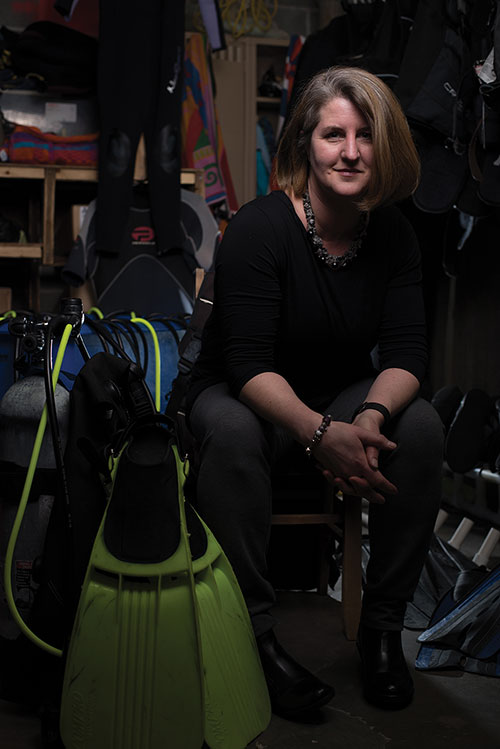 Kristin Duisberg in a closet with some SCUBA gear