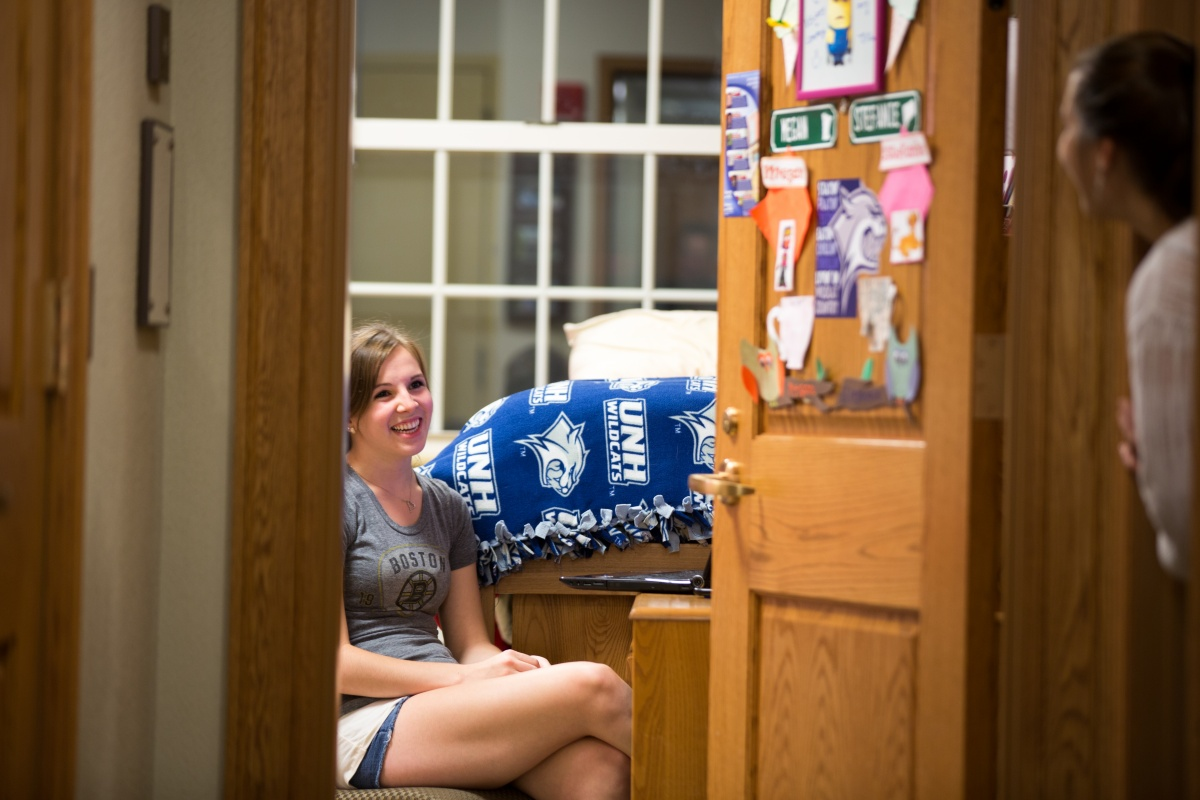 Girls chatting in dorm room with door open