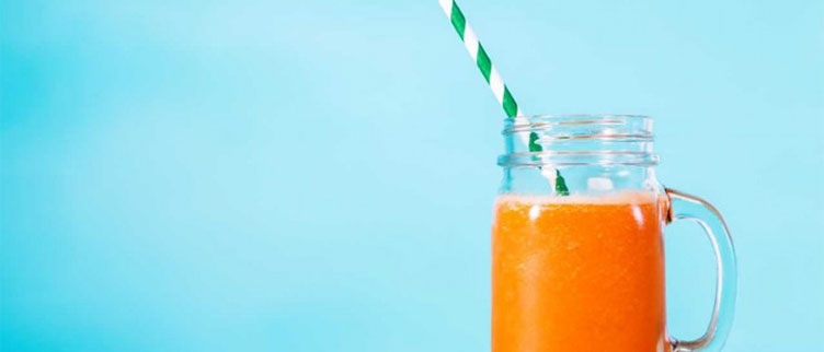 orange smoothie in front of a blue background
