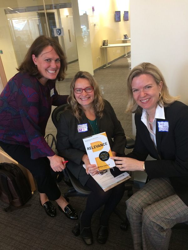 photo of 3 women holding book