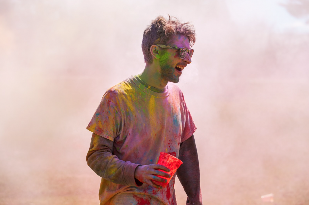 UNH student covered in colored chalk during Holi celebration