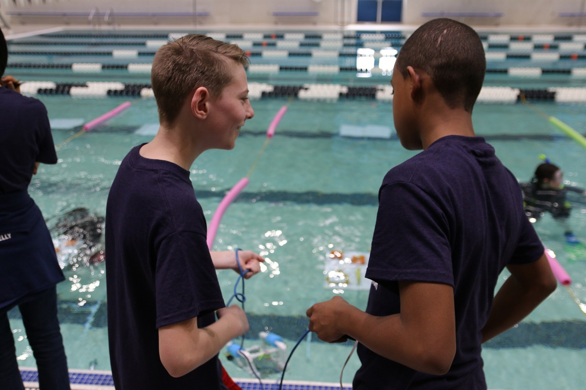 Two New Hampshire middle school students driving their underwater robots at the UNH pool