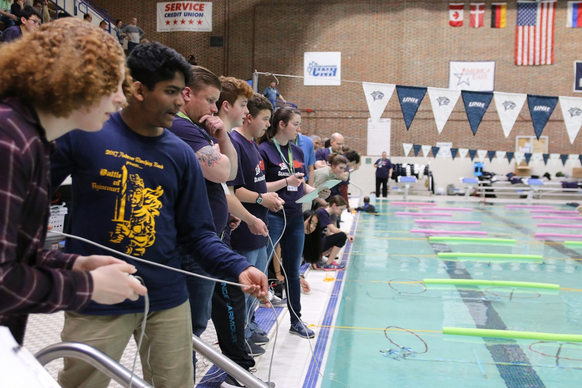 Middle school students testing their underwater robots at the UNH pool during SeaPerch challenge