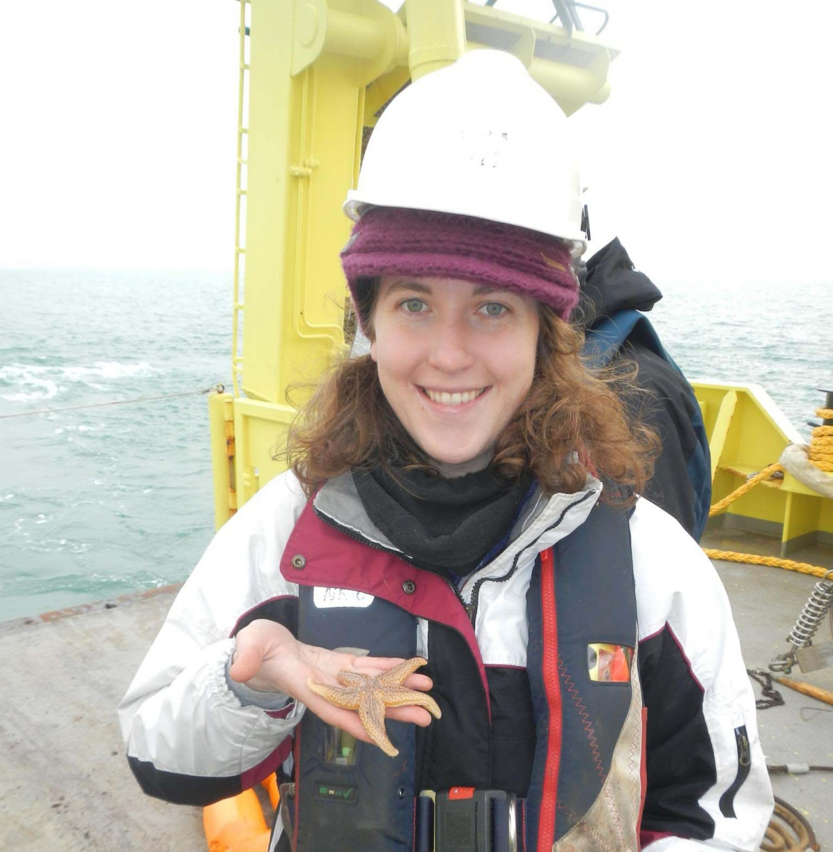 Woman on research vessel wears a hardhat and smiles while holding a seastar.