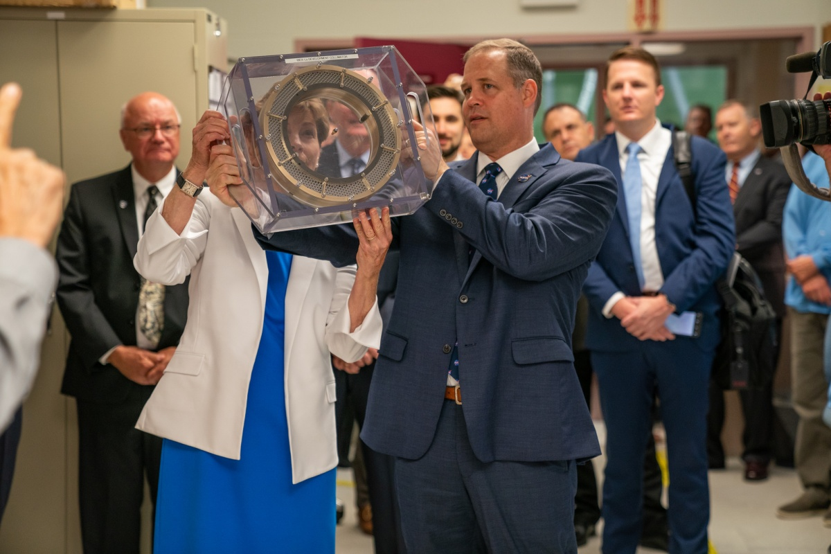Jeanne Shaheen looks through piece of space equipment as Jim Bridenstine looks on