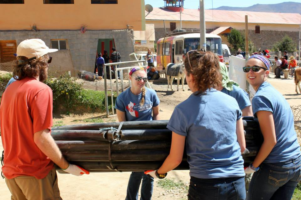 Joanna Lewis '17 carrying water pipe in Peru