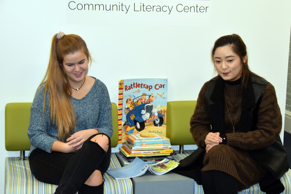 Two UNH students reading to young children