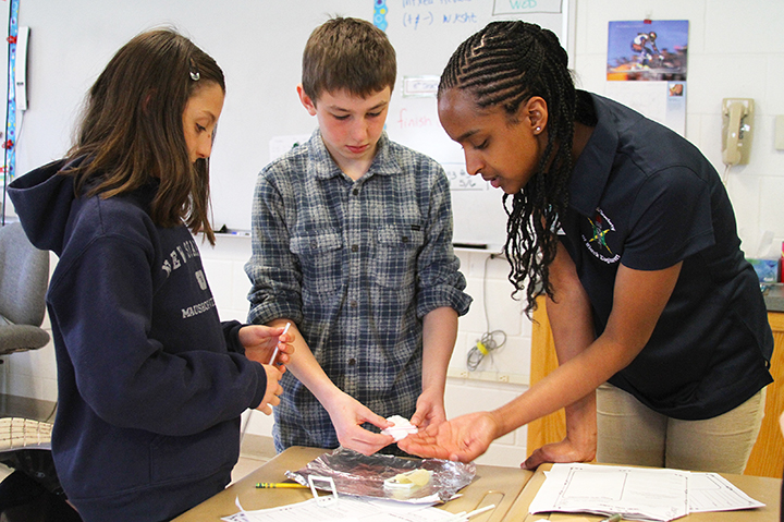 UNH engineering student Salimah Hussien with students at Greenland Central School's Engineering Day.
