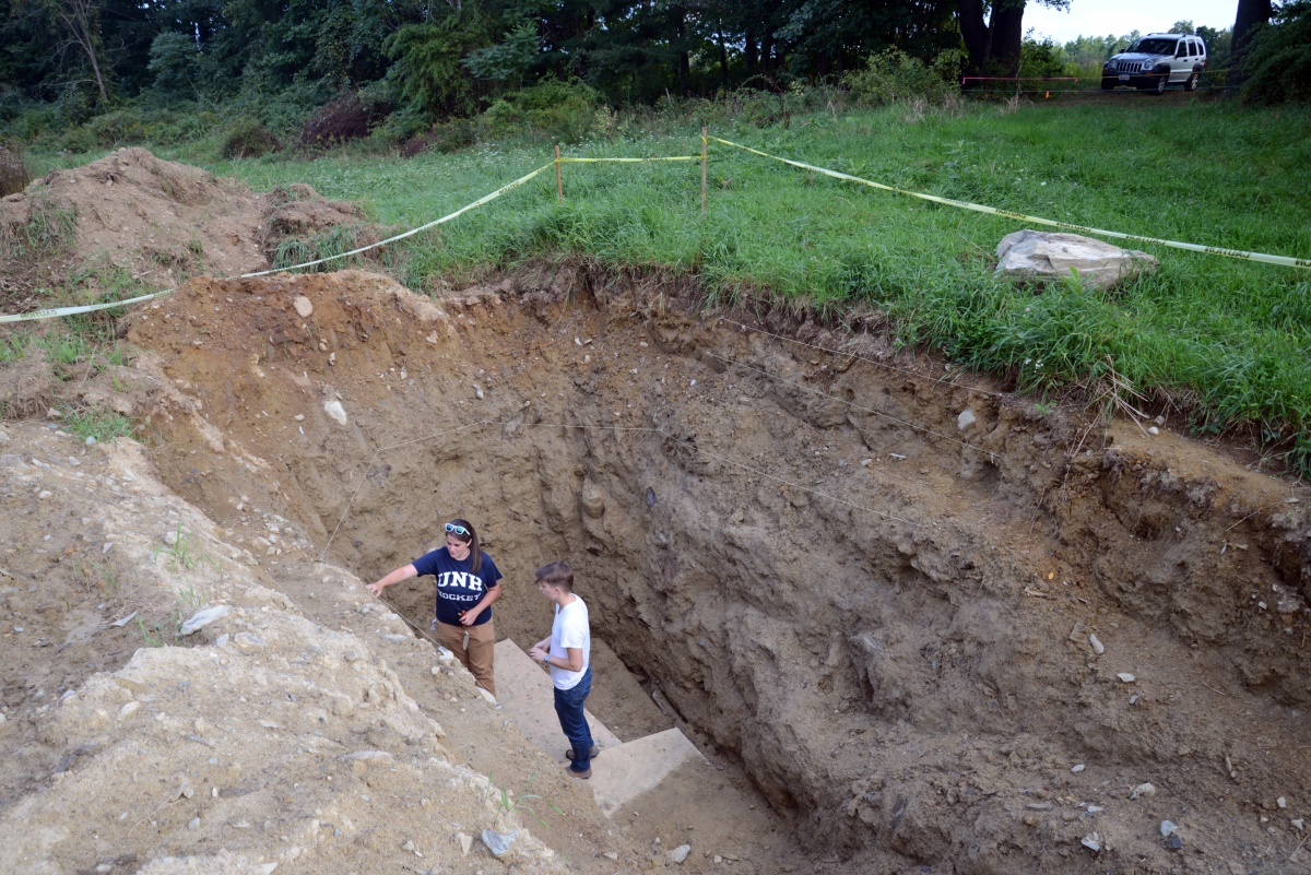 Researchers deep in an excavated hole