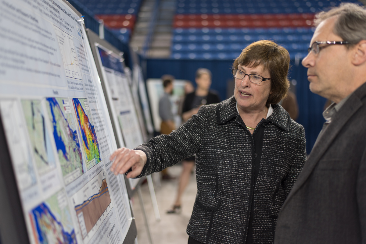 Woman in a suit explains a scientific poster to an onlooker