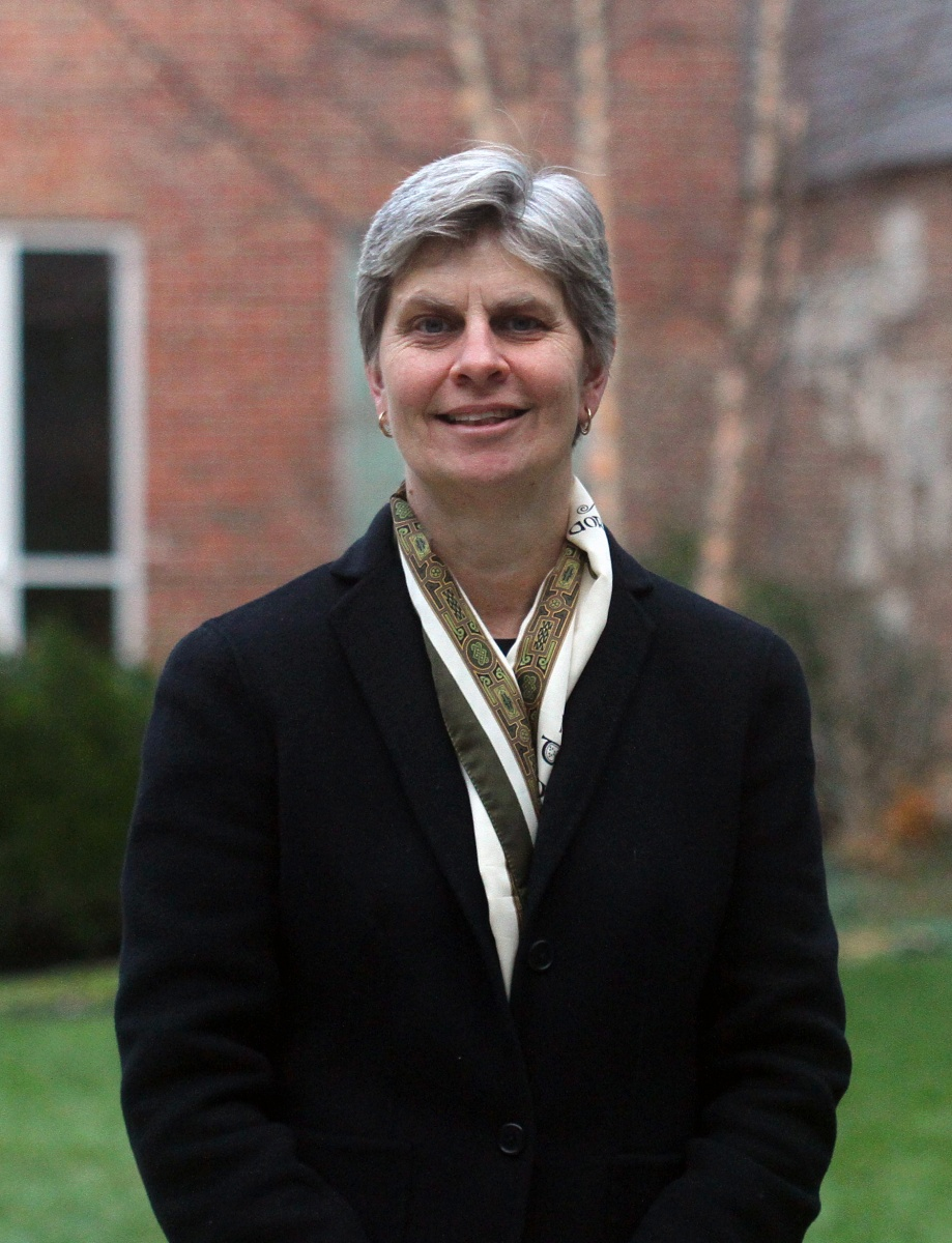 Professor Jennifer Jacobs looks at camera, wearing suit jacket and scarf