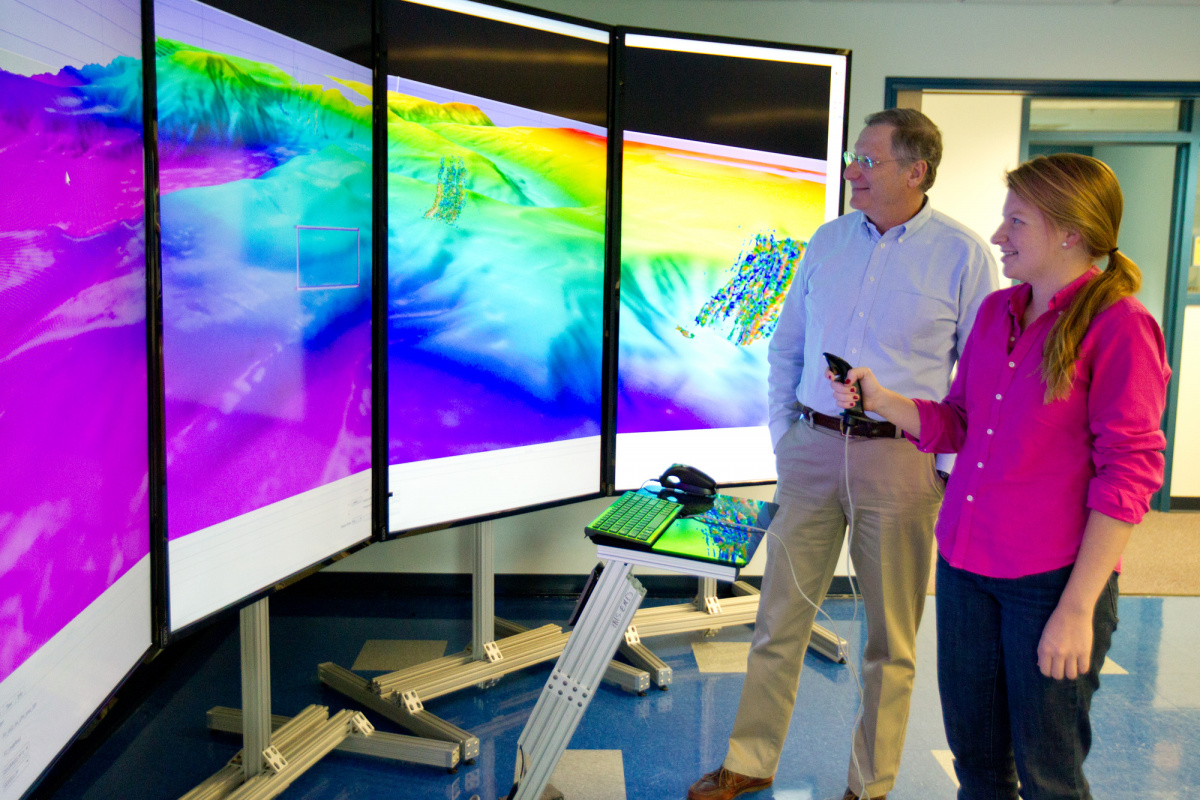Larry Mayer and a graduate student look at seafloor data on a large screen