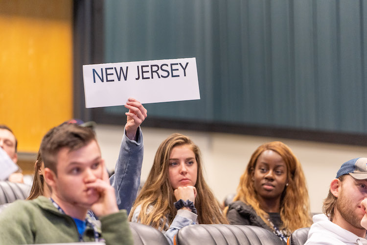 student holding up sign that reads 'New Jersey' during voting