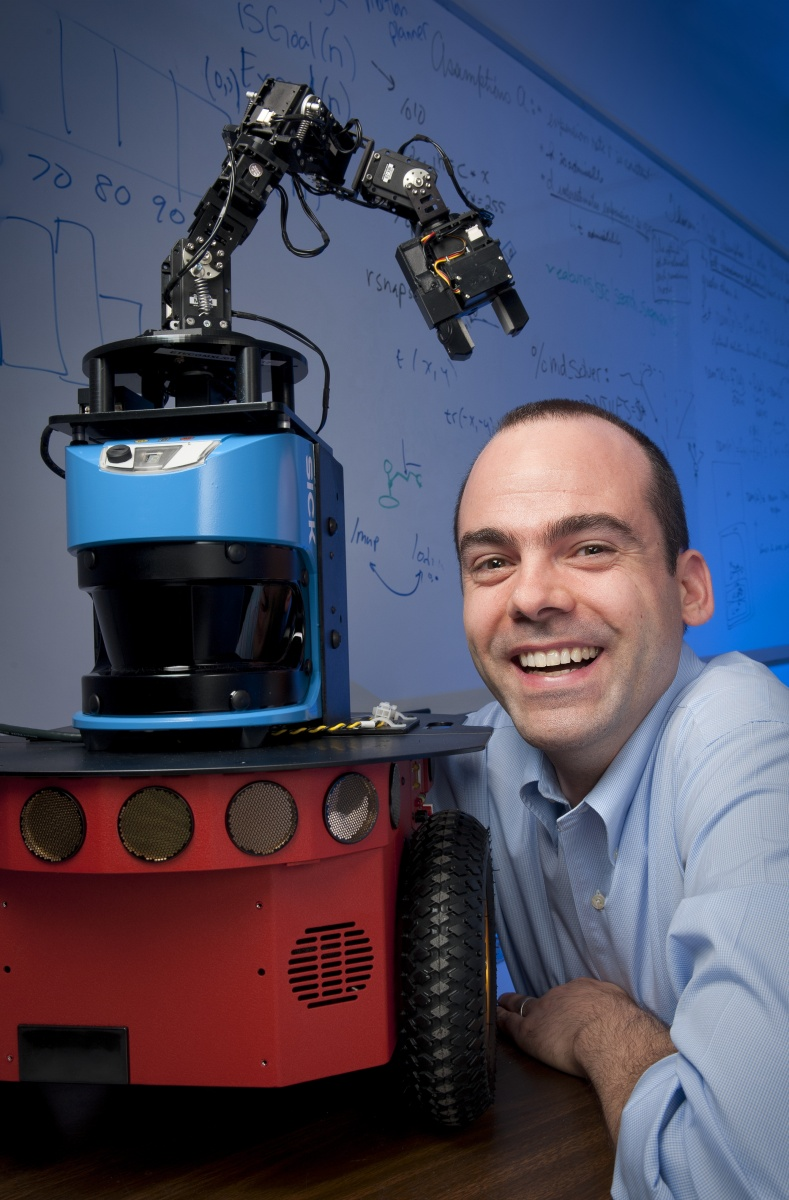 Professor Wheeler Ruml beside a robot