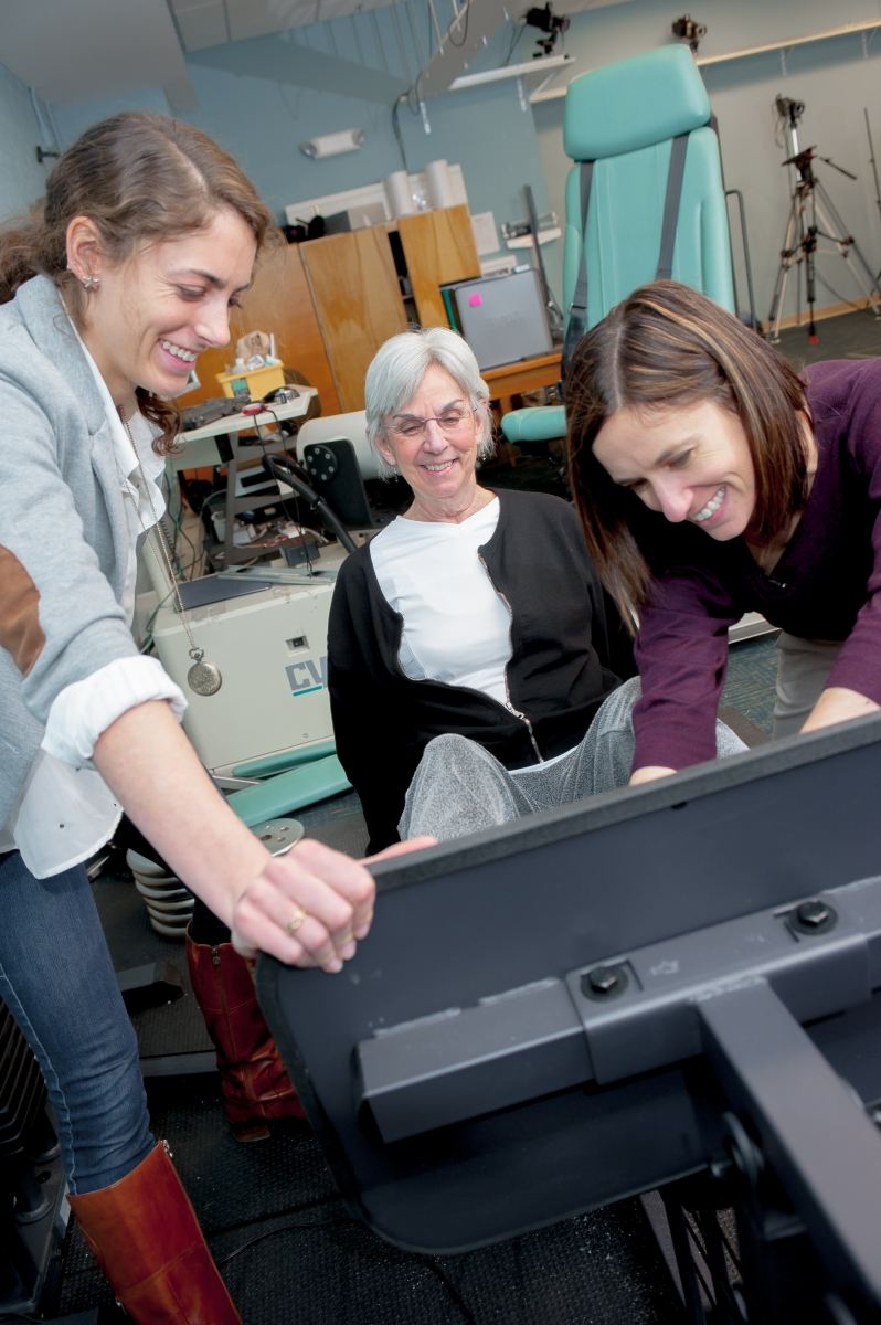 Researchers working with elderly woman on leg weights machine