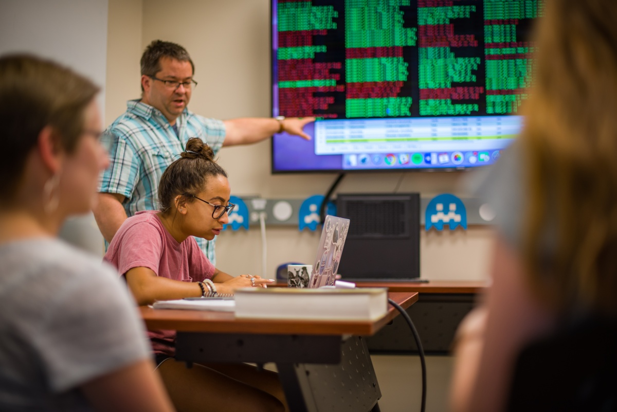 Professor and student reviewing data projected on a screen