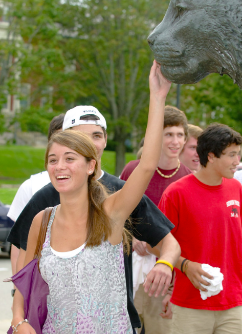 UNH student patting the Wildcat statue's nose