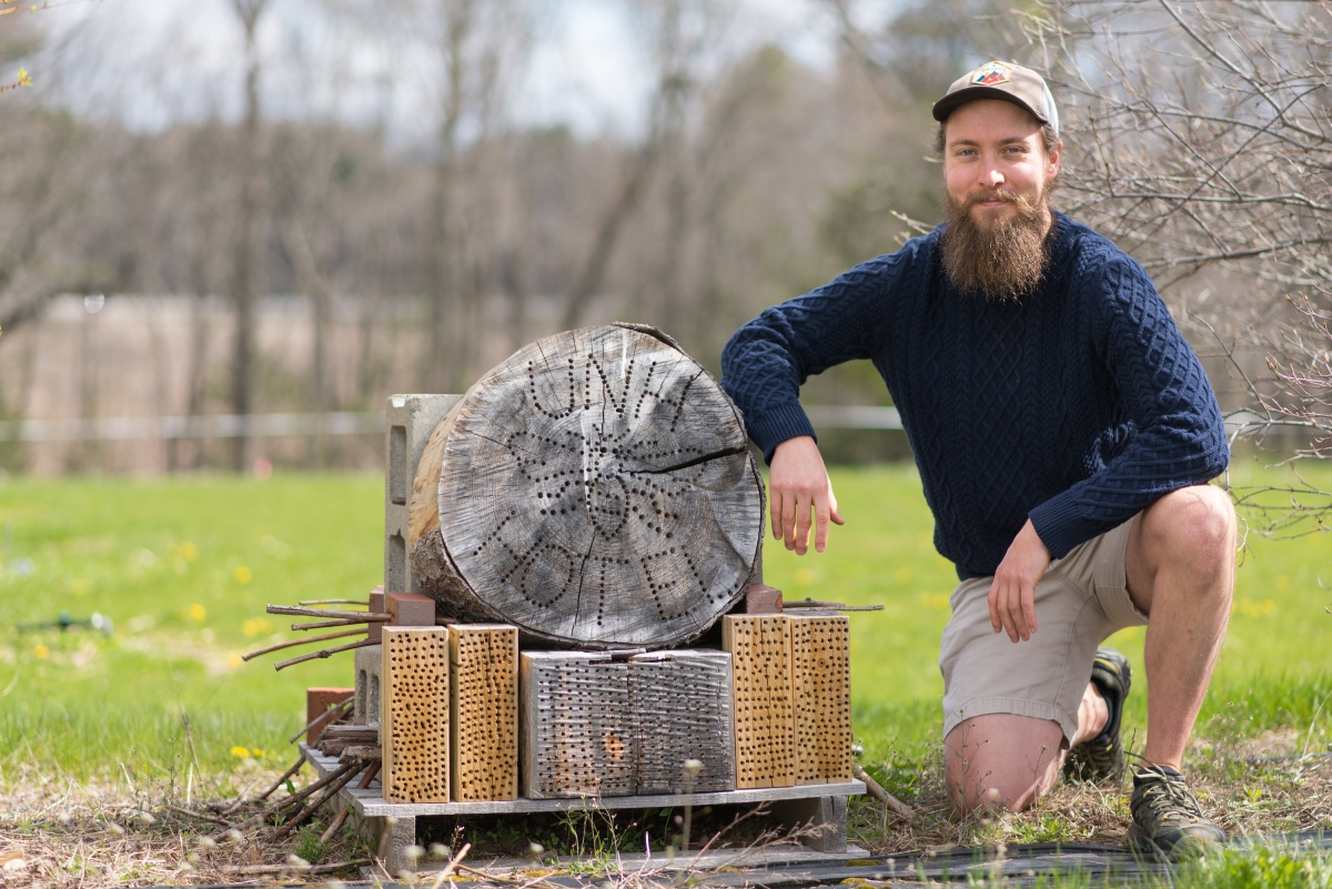 UNH grad student Wyatt Shell next to bee hotel
