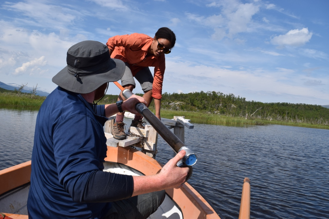 On a boat on a lake, two graduate students hold a research instrument