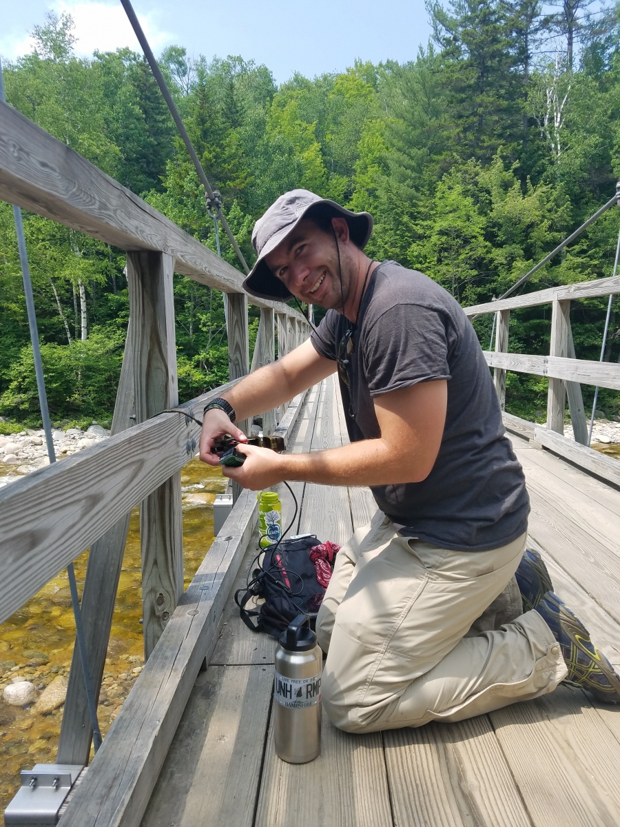 UNH researcher deploying research equipment on trail