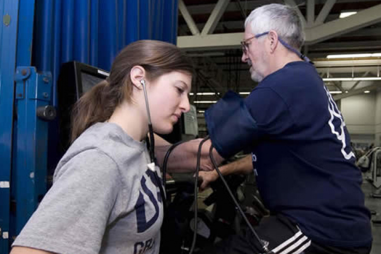 student measuring heartrate of rehab participant