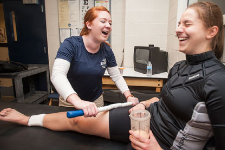 student performs atheltic therapy on hockey player