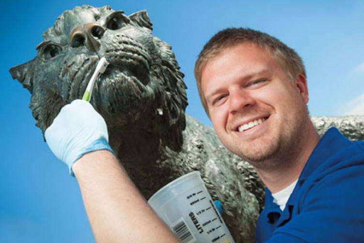jameson coop cleaning the wildcat sculpture
