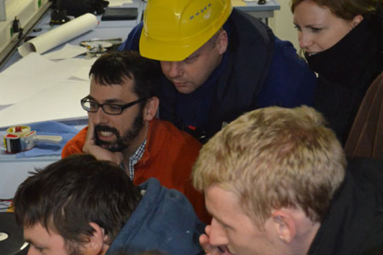 Jonathan Beaudoin (in glasses and orange sweater), research assistant professor in the University of New Hampshire's Center for Coastal and Ocean Mapping/Joint Hydrographic Center, views the underwater footage of the S.S. Terra Nova with others onboard the Schmidt Ocean Institute's R/V Falkor.