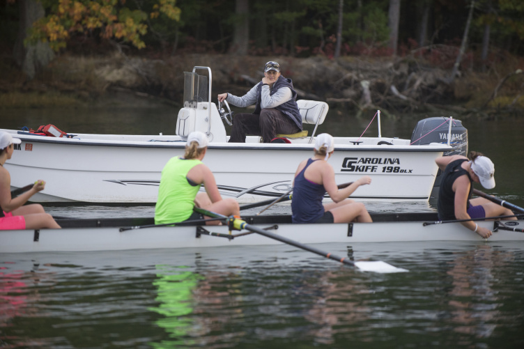 Coach in motorboat calls to four women in rowing shell