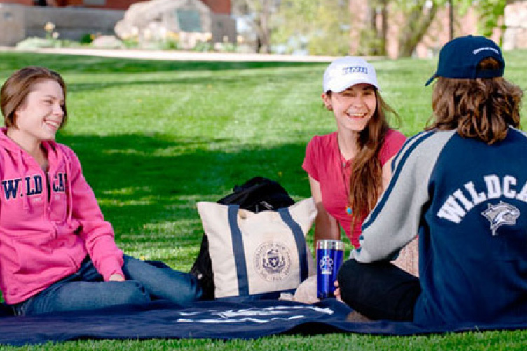 students on unh great lawn with unh purchases