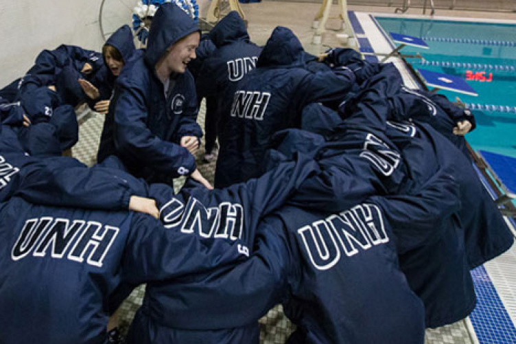 women's swimming team, huddled before a competition