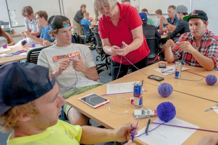 students knitting purple caps for babies