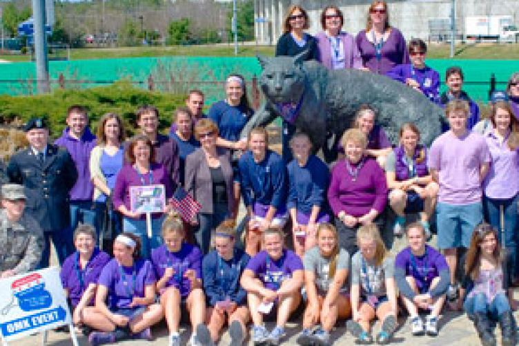 cooperative extention volunteers in front of cat sculpture