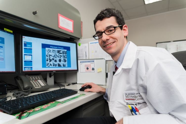 Adam DiPippo performing research on his computer at his residency at University of Texas MD Anderson Cancer Center in Houston