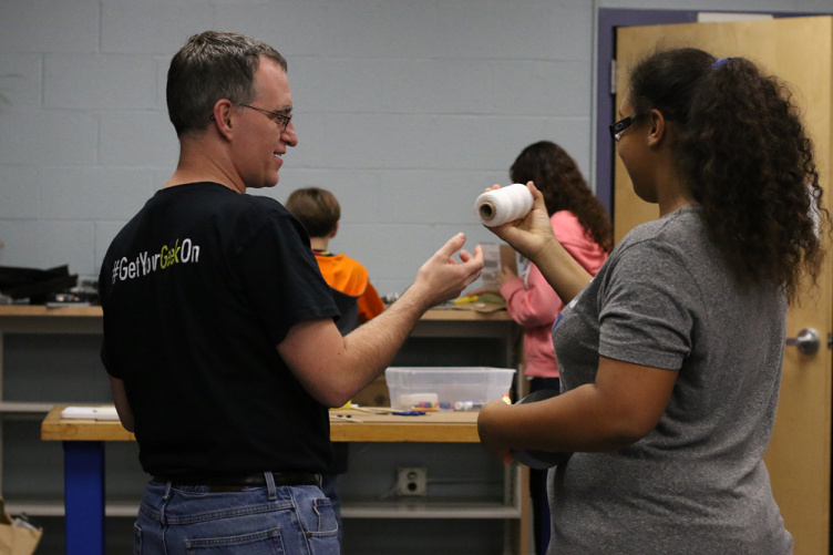STEM docent Eric Swanson works with student.